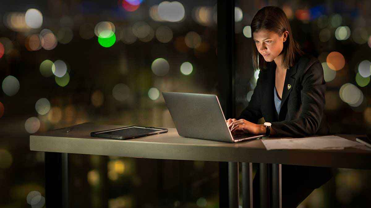 White woman working at a laptop after dark