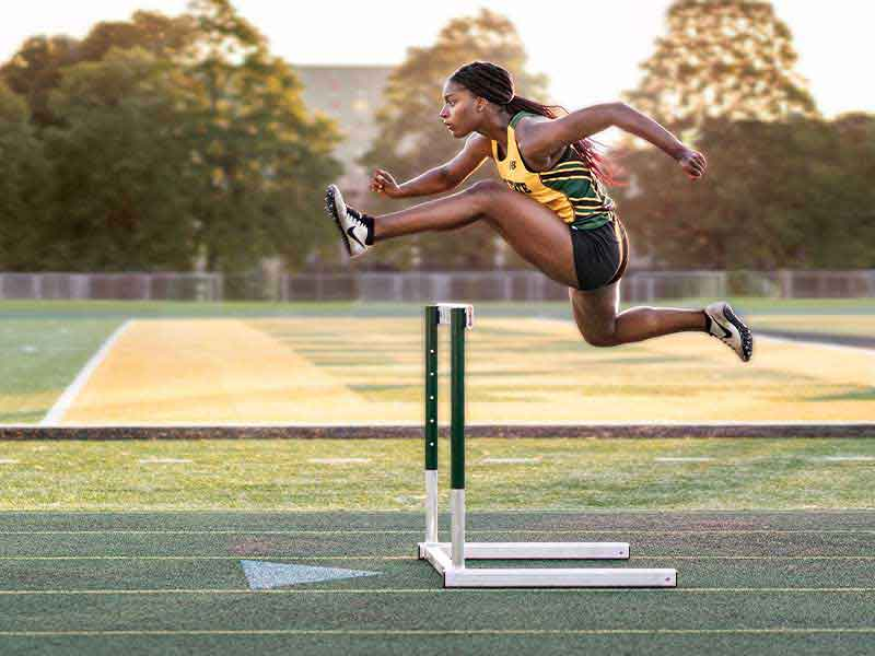 African-American woman jumping over a hurdle on an outdoor track